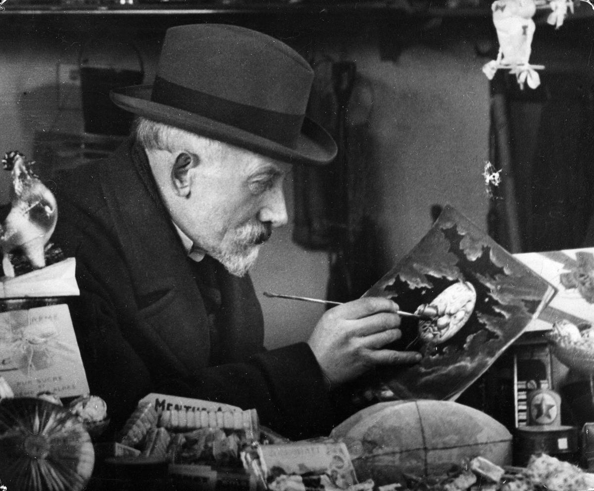 """Méliès dans la boutique de la gare Montparnasse, dessinant l'icone du """"Voyage dans la Lune"""""""